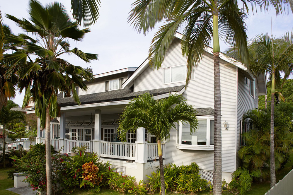 An exterior shot of Manoa Senior Care. The building is white with a covered patio. Greenery lines the front yard.